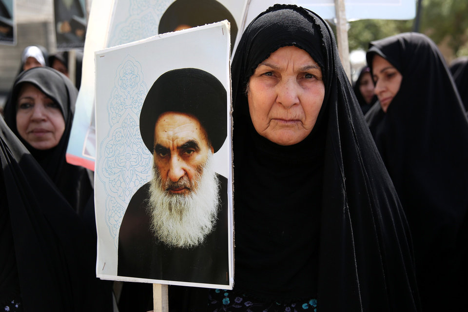 Photo - An Iraqi woman living in Iran holds a poster of the Grand Ayatollah Ali al-Sistani, Iraq's top Shiite cleric, in a demonstration against Sunni militants of the al-Qaida-inspired Islamic State of Iraq and the Levant, or ISIL, and to support Ayatollah al-Sistani, in Tehran, Iran, Friday, June 20, 2014. (AP Photo/Ebrahim Noroozi)