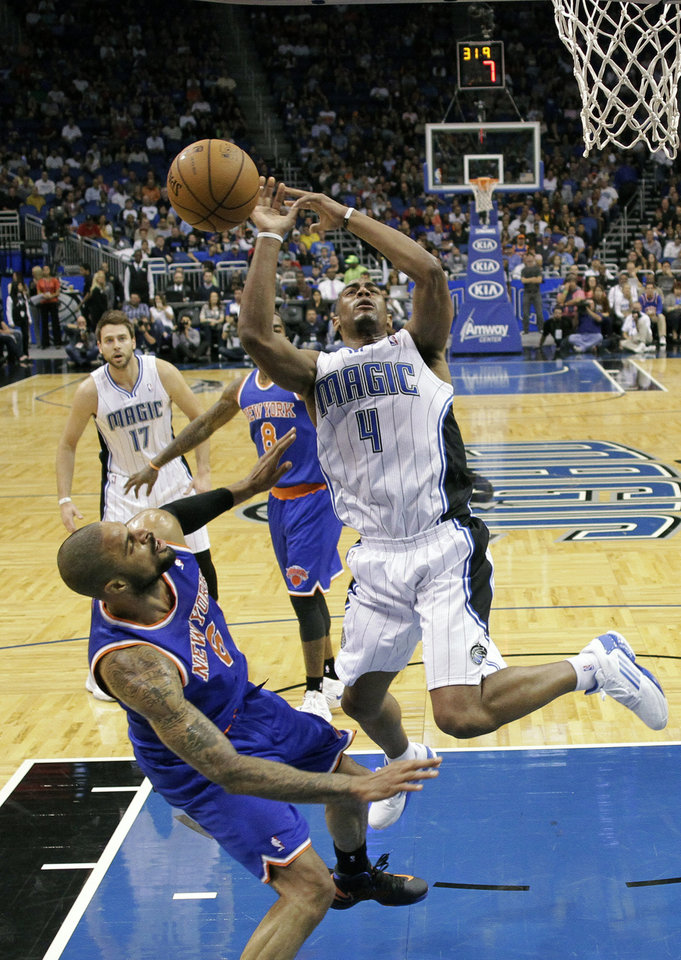 Photo -   Orlando Magic's Arron Afflalo (4) loses control of the ball as he collides with New York Knicks' Tyson Chandler, lower left, during the first half of an NBA basketball game, Tuesday, Nov. 13, 2012, in Orlando, Fla. (AP Photo/John Raoux)