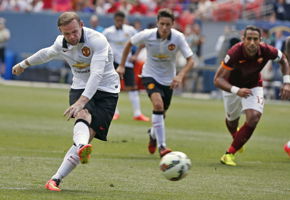 Photo - Manchester United's Wayne Rooney, left, kicks for a goal during the first half of an exhibition soccer match against AS Roma at Mile High Stadium, in Denver, Saturday, July 26, 2014. (AP Photo/Brennan Linsley)