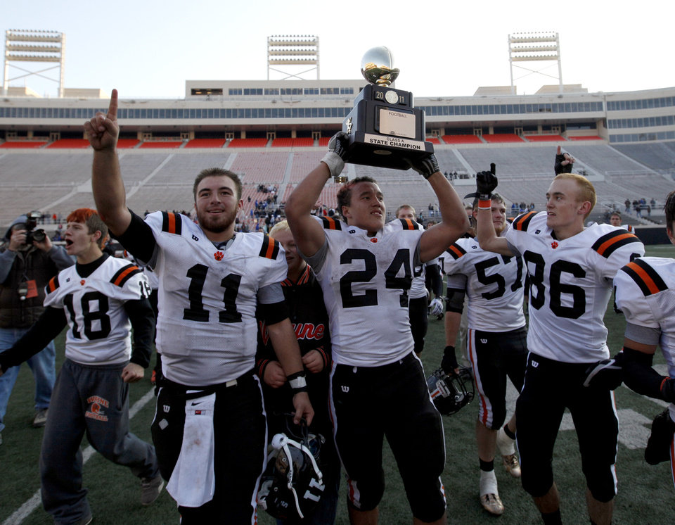 Photo - CLASS A HIGH SCHOOL FOOTBALL STATE CHAMPIONSHIP / CELEBRATION: Wayne's Josh Way holds up the championship trophy as Sam Martin (11) and Justin Rafferty (86) celebrate after defeating Woodland in the  Class A state championship high school football game at Boone Pickens Stadium in Stillwater, Okla., Saturday, Dec. 10, 2011. Photo by Sarah Phipps, The Oklahoman