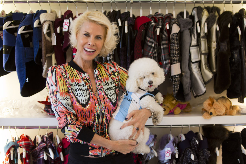 Photo - Karen Reichardt, owner of a pet store, poses with her dog wearing a garment resembling the jersey of the Argentine national soccer squad in Buenos Aires, Argentina, Thursday, June 5, 2014. Reichardt designed a number of garments for pets ahead of the World Cup that starts next week in Brazil. (AP Photo/Victor R. Caivano)
