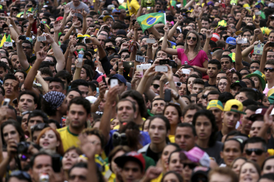 Photo - Brazil soccer fans watch their team's World Cup semifinal match with Germany via live telecast in Belo Horizonte, Brazil, Tuesday, July 8, 2014. (AP Photo/Bruno Magalhaes)