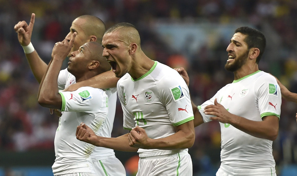 Photo - Algeria's Yacine Brahimi, front left, celebrates after scoring his side's fourth goal during the group H World Cup soccer match between South Korea and Algeria at the Estadio Beira-Rio in Porto Alegre, Brazil, Sunday, June 22, 2014. (AP Photo/Martin Meissner)