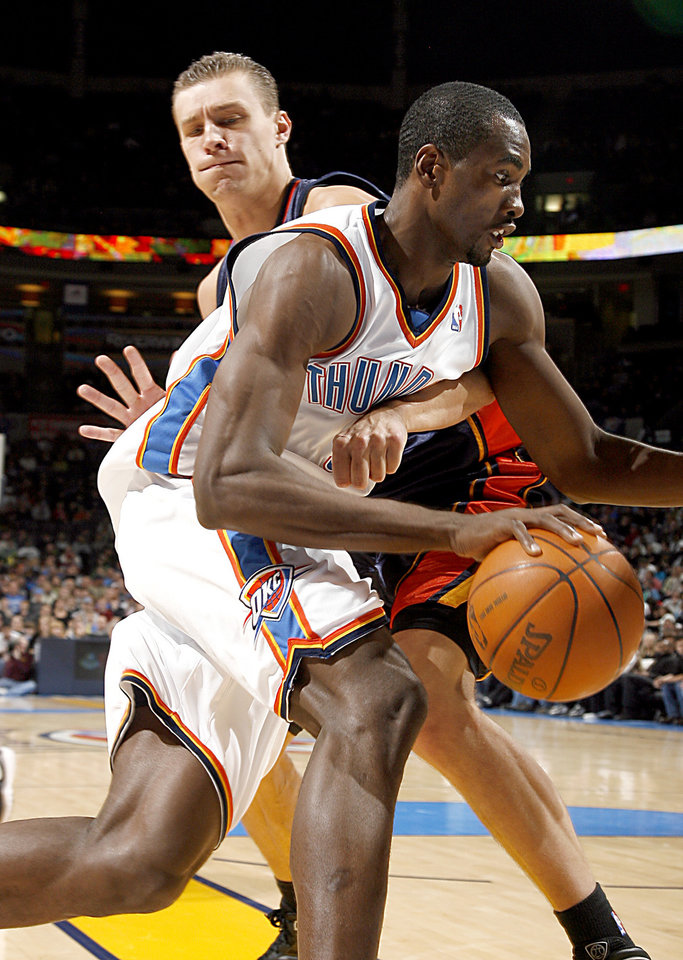Photo - Oklahoma City's Serge Ibaka (9) tries to get by Golden State's Andris Biedrins (15) during the NBA game between the Oklahoma City Thunder and Golden State Warriors, Sunday, Jan. 31, 2010, at the Ford Center in Oklahoma City. Photo by Sarah Phipps, The Oklahoman