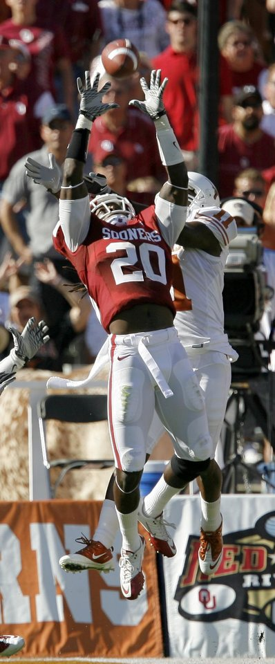 Photo - OU's Quinton Carter intercepts a pass in front of James Kirkendoll of Texas during the first half of the Red River Rivalry college football game between the University of Oklahoma Sooners (OU) and the University of Texas Longhorns (UT) at the Cotton Bowl on Saturday, Oct. 2, 2010, in Dallas, Texas.   Photo by Bryan Terry, The Oklahoman