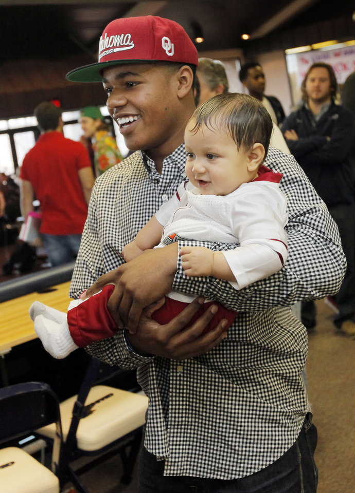 Photo - Heritage Hall's Sterling Shepard holds his 9-month-old cousin Drake Shepard after the National Signing Day ceremony at Heritage Hall in Oklahoma City, Wednesday, Feb. 1, 2012. Sterling Shepard signed to play football at the University of Oklahoma. Photo by Nate Billings, The Oklahoman