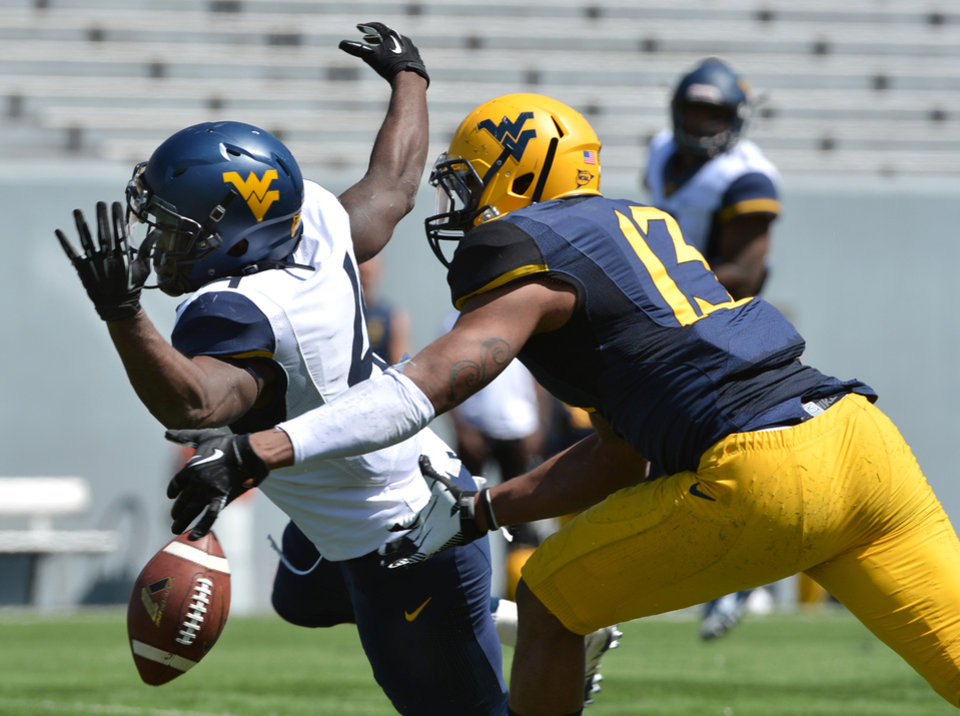 Photo - West Virginia's Wendell Smallwood (4) can't hold onto a pass while defended by Sean Williams (13) during spring NCAA college football game in Morgantown, W.Va., Saturday, April 12, 2014. (AP Photo/Craig Cunningham)