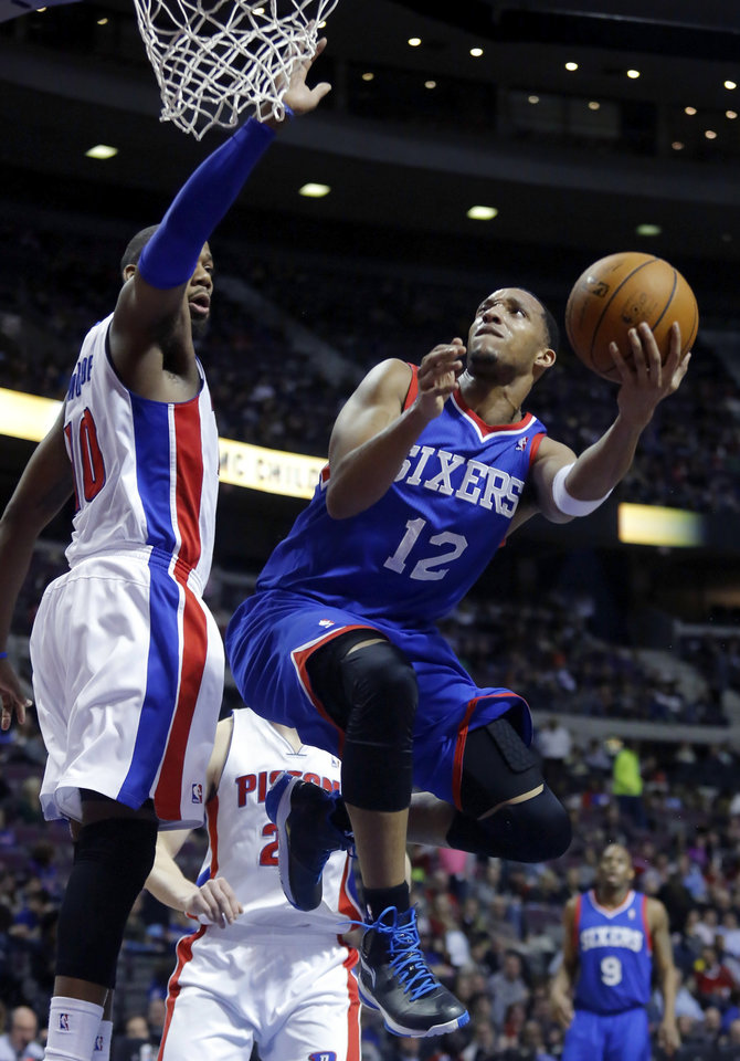 Photo - Philadelphia 76ers forward Evan Turner (12) goes to the basket against Detroit Pistons center Greg Monroe (10) during the first half of an NBA basketball game Saturday, Feb. 1, 2014, in Auburn Hills, Mich. (AP Photo/Duane Burleson)