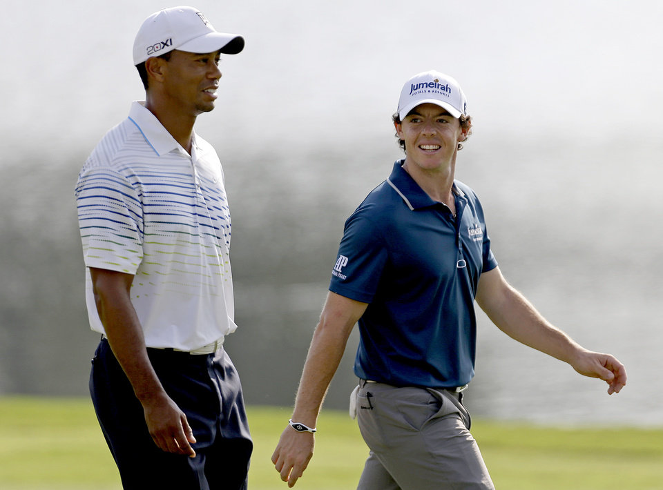 Photo -   Tiger Woods, left, and Rory McIlroy, of Northern Ireland, walk up the fairway of the 17th hole during the first round at the Tour Championship golf tournament, Thursday, Sept. 20, 2012, in Atlanta. (AP Photo/David Goldman)