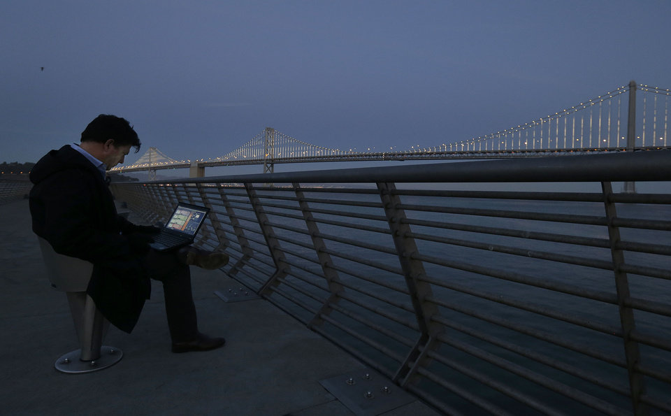 In this Wednesday, Feb. 20, 2013,  photo, Artist Leo Villareal poses for photographs as he operates lights on the San Francisco-Oakland Bay Bridge on Pier 14 in San Francisco. The San Francisco-Oakland Bay Bridge has been turned into the latest, and by far the biggest, backdrop for New York artist Leo Villareal, who has individually programmed 25,000 white lights spaced a foot apart on 300 of the span�s vertical cables to create what is being billed as the world�s largest illuminated sculpture. (AP Photo/Jeff Chiu)