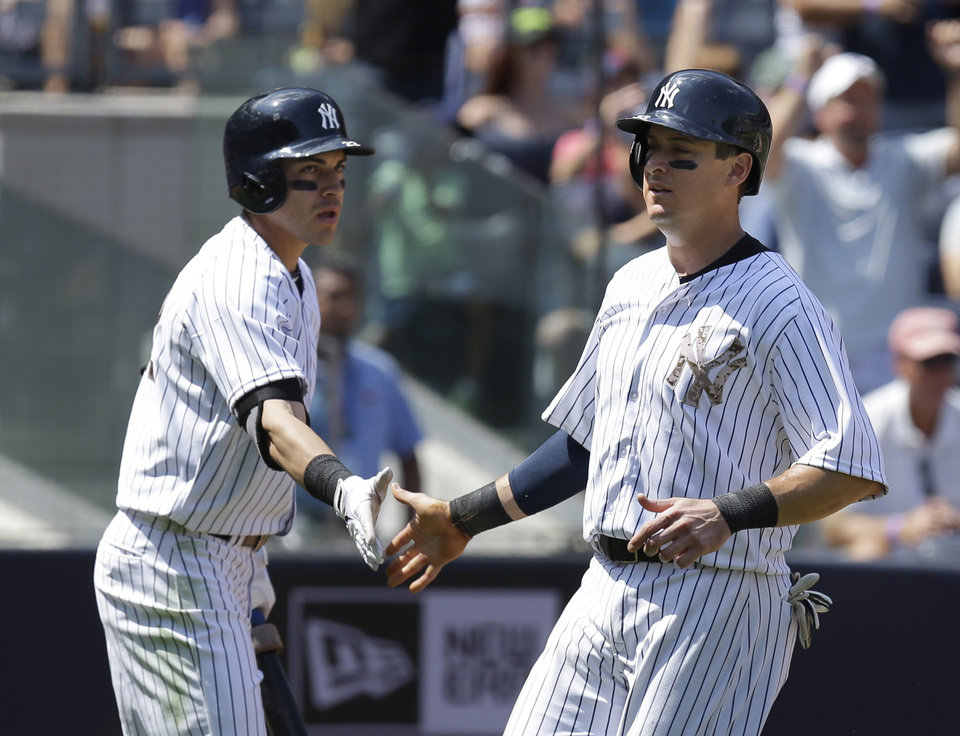 Photo - New York Yankees' Kelly Johnson, right, celebrates with Jacoby Ellsbury after scoring during the fifth inning of a baseball game against the Cincinnati Reds at Yankee Stadium on Sunday, July 20, 2014, in New York. (AP Photo/Seth Wenig)