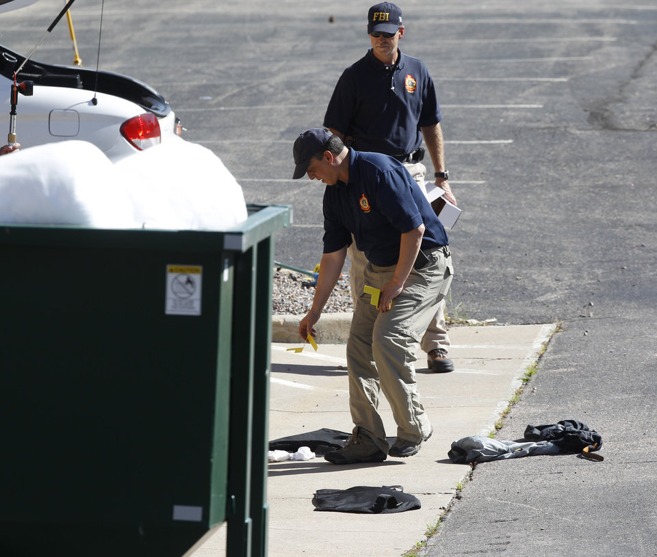 Photo - Investigators place evidence markers at the Century 16 theatre east of the Aurora Mall in Aurora, Colo., on Friday, July 20, 2012. (AP Photo/David Zalubowski) ORG XMIT: CODZ110