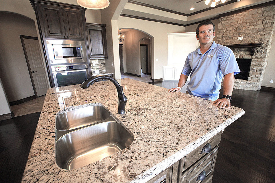 Photo - Russell Clark of R&R Homes shows the kitchen island at the Moore Home Builders Association's project house for the Showcase of Homes, at 1105 Dayton Lane in Moore.  David McDaniel - The Oklahoman