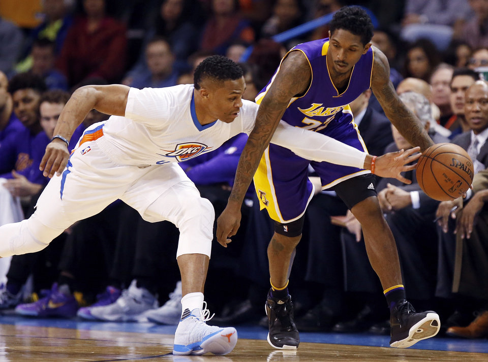 Photo - Oklahoma City's Russell Westbrook (0) tries to steal the ball from Los Angeles' Lou Williams (23) during an NBA basketball game between the Oklahoma City Thunder and the Los Angeles Lakers at Chesapeake Energy Arena in Oklahoma City, Saturday, Dec. 19, 2015. Photo by Nate Billings, The Oklahoman