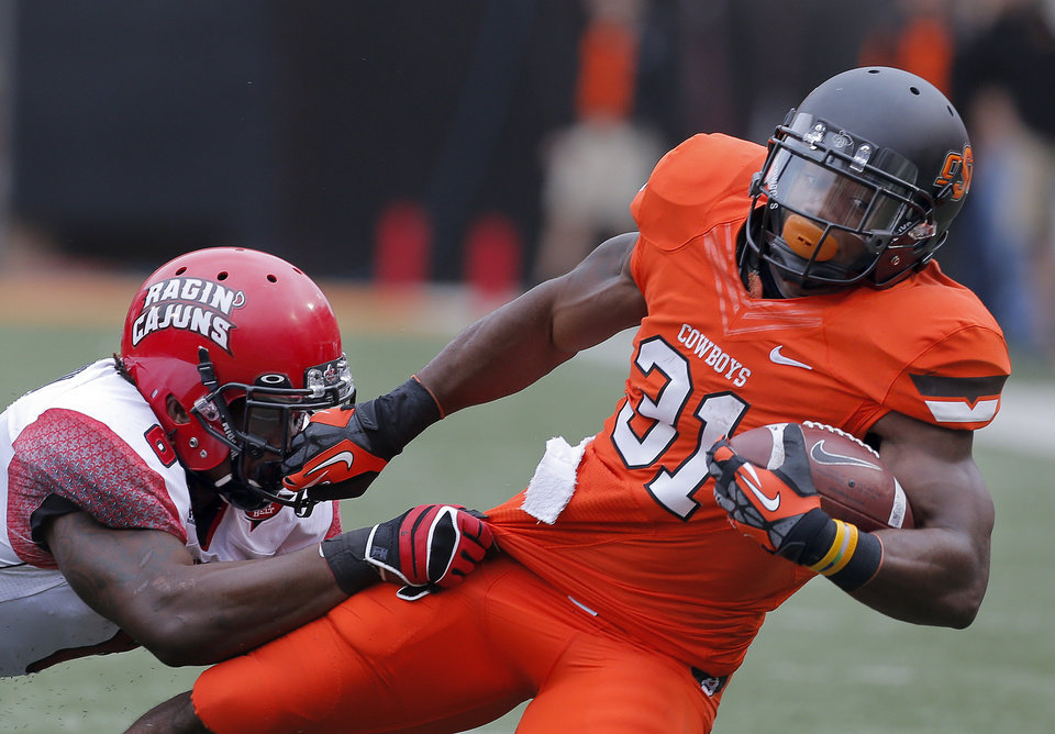 Oklahoma State\'s Jeremy Smith (31) is tackled is tackled by Louisiana-Lafayette\'s Chris Hill (8) during a college football game between Oklahoma State University (OSU) and the University of Louisiana-Lafayette (ULL) at Boone Pickens Stadium in Stillwater, Okla., Saturday, Sept. 15, 2012. Photo by Sarah Phipps, The Oklahoman