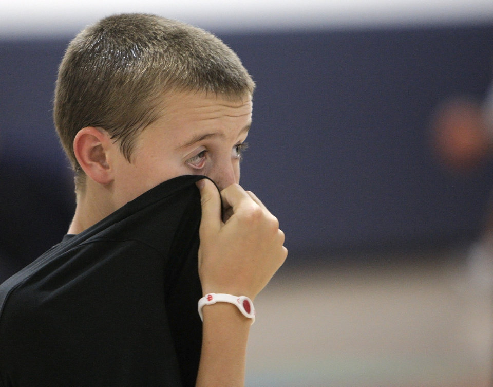 Photo - Ben Carllson, 13 of Edmond, wipes sweat off of his face during the Blake Griffin basketball camp at the Santa Fe Family Life Center in Oklahoma City Thursday, Aug. 4, 2011.  Photo by Garett Fisbeck, The Oklahoman