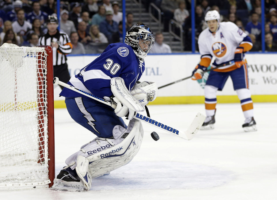 Photo - Tampa Bay Lightning goalie Ben Bishop (30) makes a save on a shot as New York Islanders right wing Kyle Okposo (21) closes in during the first period of an NHL hockey game, Thursday, Jan. 16, 2014, in Tampa, Fla. (AP Photo/Chris O'Meara)