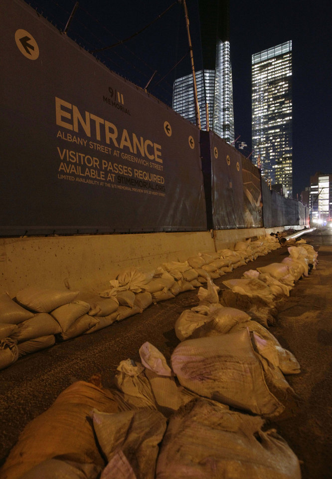 Sandbags rim the perimeter of the World Trade Center Memorial and construction site after the memorial was closed by flooding in the wake of Superstorm Sandy, Monday, Nov. 5, 2012, in New York. Joe Daniels, president of the National September 11 Memorial and Museum, said that water that rushed into the site has been pumped out and the memorial will reopen to the public Tuesday. (AP Photo/Kathy Willens)