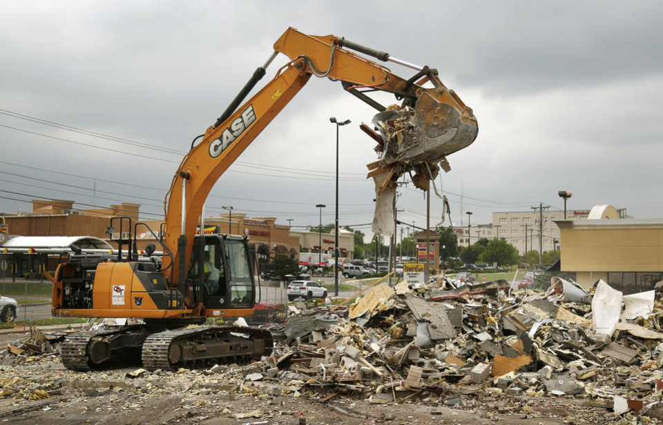 Photo -  A demolition crew tears apart one of the buildings in the Bryant Square shopping center at Second Street and Bryant Avenue. Planet Sub once was located in this building. [PHOTO BY PAUL HELLSTERN, THE OKLAHOMAN]