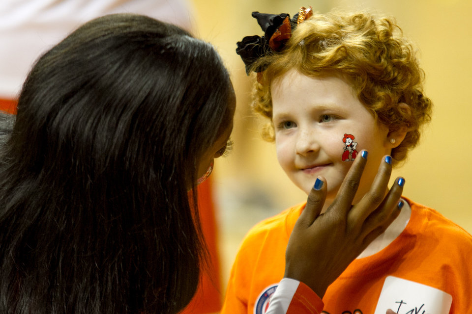 Iniki Allen puts a Pistol Pete sticker on Taylor Brandt's cheek.  Oklahoma State University hosted a Coachs vs. Cancer Birthday party in Gallagher-Iba arena in Stillwater, Ok on Sept. 16, 2012. Photos by Mitchell Alcala for the Oklhaoman