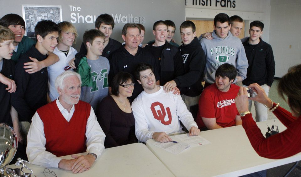 Photo - Gabe Ikard, Bishop McGuinness, poses for a photo with his father Jim, mother Becky , brother Sam and the senior football players after signing a letter of intent with OU, Wednesday, February 4, 2009.  Photo by David McDaniel/The Oklahoman