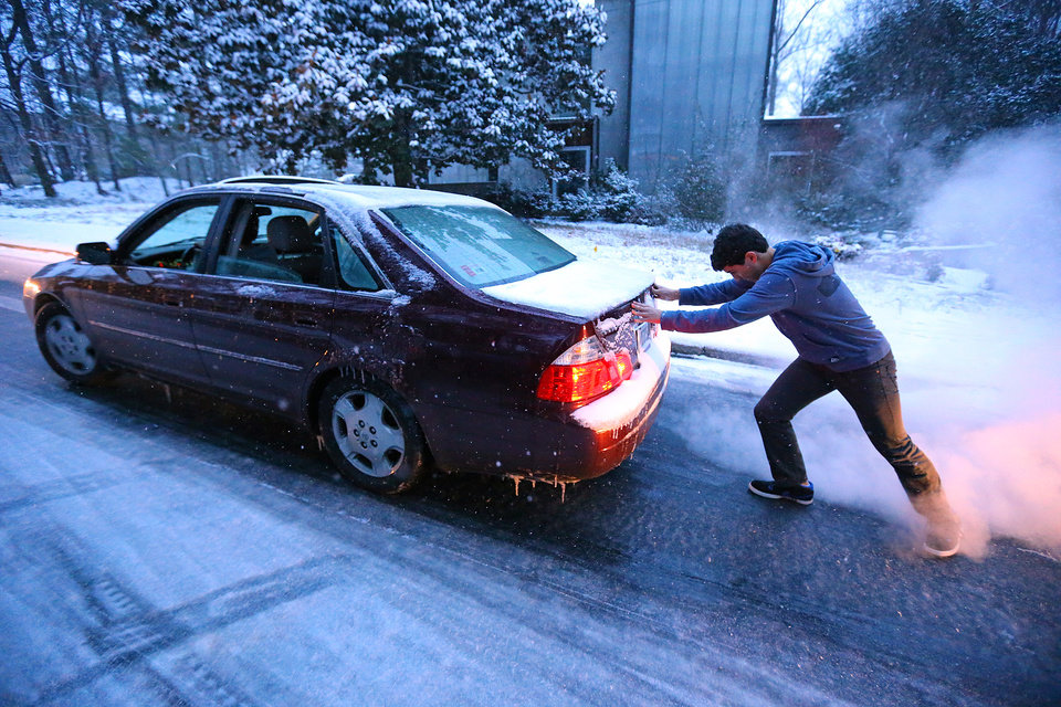 Photo - Good Samaritan Sammy Rouchdi pushes stranded motorist Cameron Scheeler up an iced over hill on Womack Road after he became stuck on the ice trying to get home on Tuesday, Jan. 28, 2014, in Dunwoody.   (AP Photo/Atlanta Journal-Constitution, Curtis Compton)
