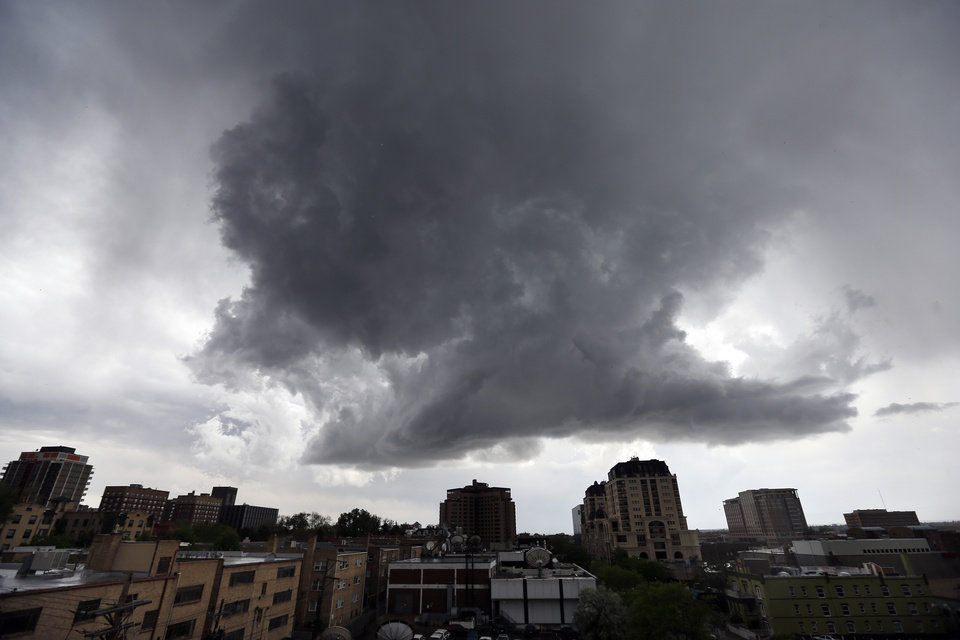 Photo - A thunderhead forms over downtown Denver, Thursday May 22, 2014. More spring thunderstorms began rolling into the Front Range and eastern Colorado on Thursday, a day after six tornadoes touched down east of Denver. Heavy hail was reported in Red Feather Lakes northwest of Fort Collins, and more hail is falling in Denver.(AP Photo/Brennan Linsley)