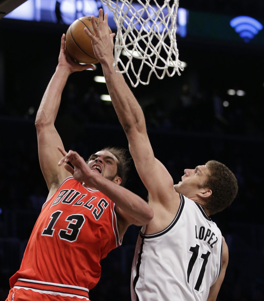 Photo - Brooklyn Nets center Brook Lopez (11) defends a shot by Chicago Bulls center Joakim Noah (13) in the second half of Game 2 of their first-round NBA basketball playoff series, Monday, April 22, 2013, in New York. The Bulls won 90-82. (AP Photo/Kathy Willens)