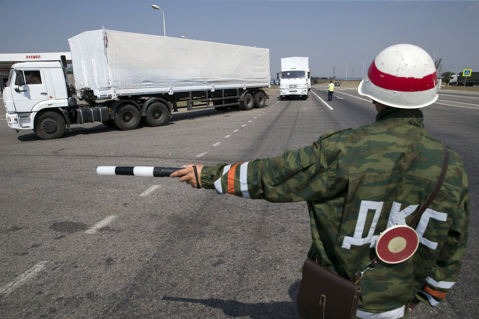 Photo - A convoy of white trucks with humanitarian aid is seen at the Ukrainian border in Rostov-on-Don region, Russia, Thursday, Aug. 14, 2014. A large Russian aid convoy resumed its journey toward Ukraine Thursday, taking a road leading directly toward a border crossing controlled by pro-Russian rebels in the Luhansk region. (AP Photo/Pavel Golovkin)
