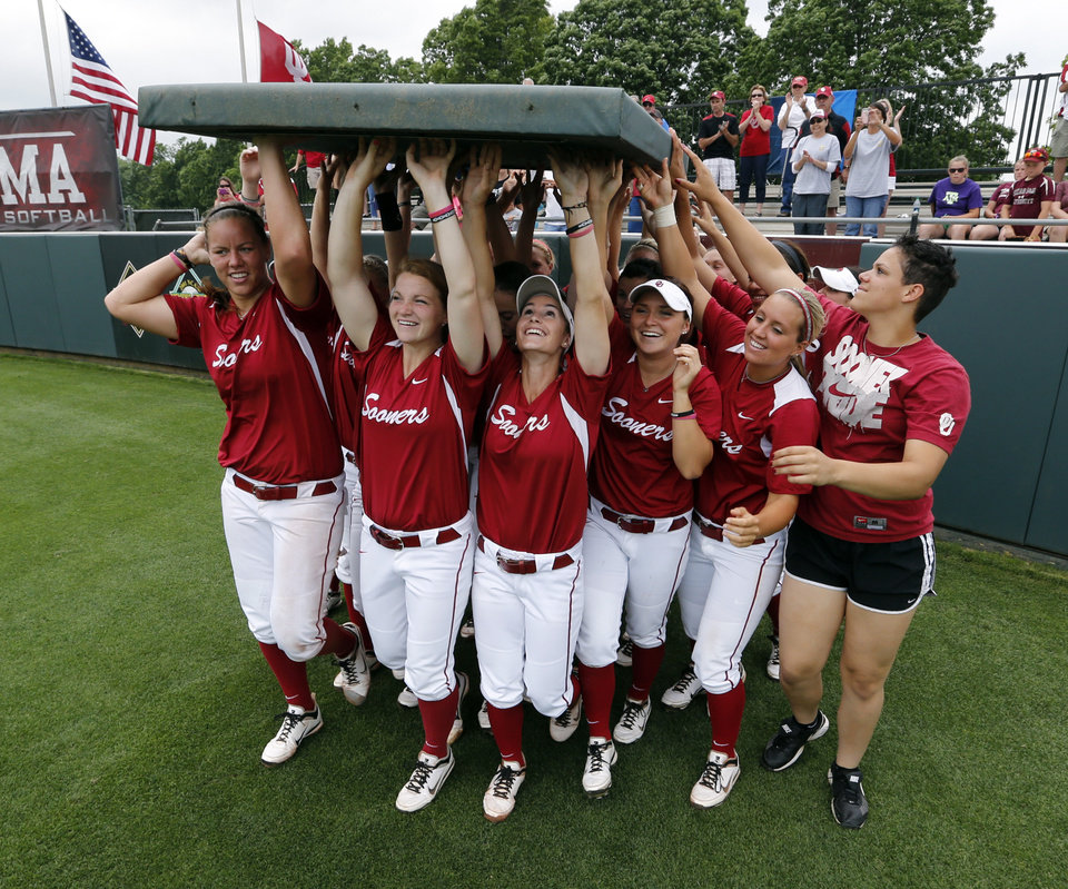 Photo - Sooner players remove an outfield panel and claim it for their own championship graphic after the NCAA Super Regional softball game as the University of Oklahoma (OU) Sooners defeat Texas A&M 8-0 at Marita Hines Field on Saturday, May 25, 2013 in Norman, Okla. to advance to the College World Series.  Photo by Steve Sisney, The Oklahoman