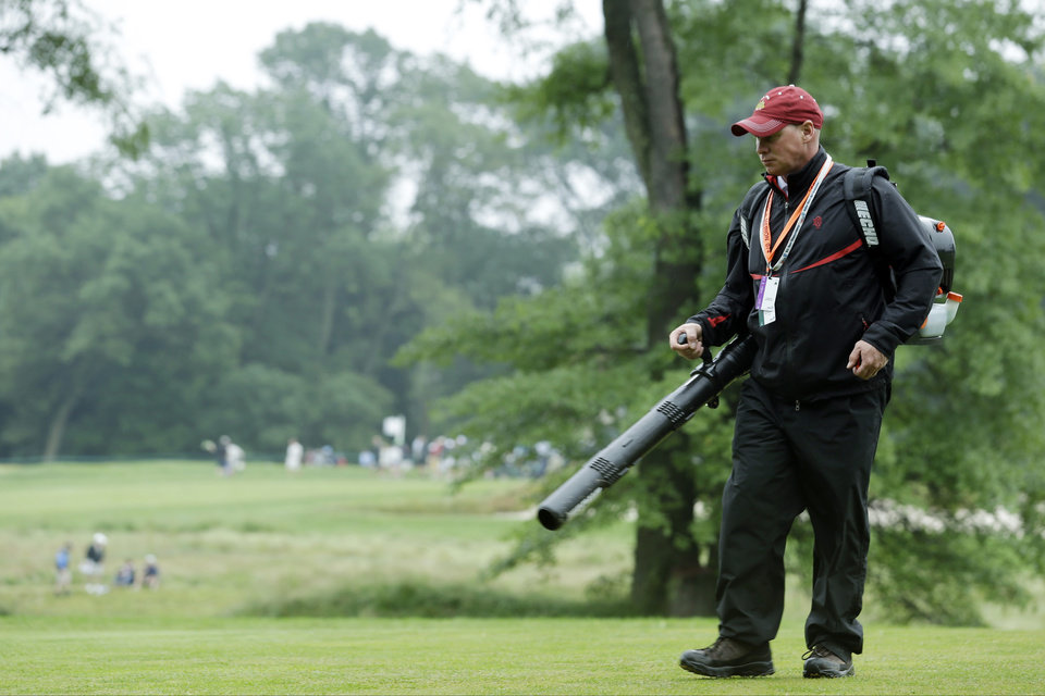 Photo - A course worker clears debris from the second hole after a weather delay during the first round of the U.S. Open golf tournament at Merion Golf Club, Thursday, June 13, 2013, in Ardmore, Pa. (AP Photo/Julio Cortez)