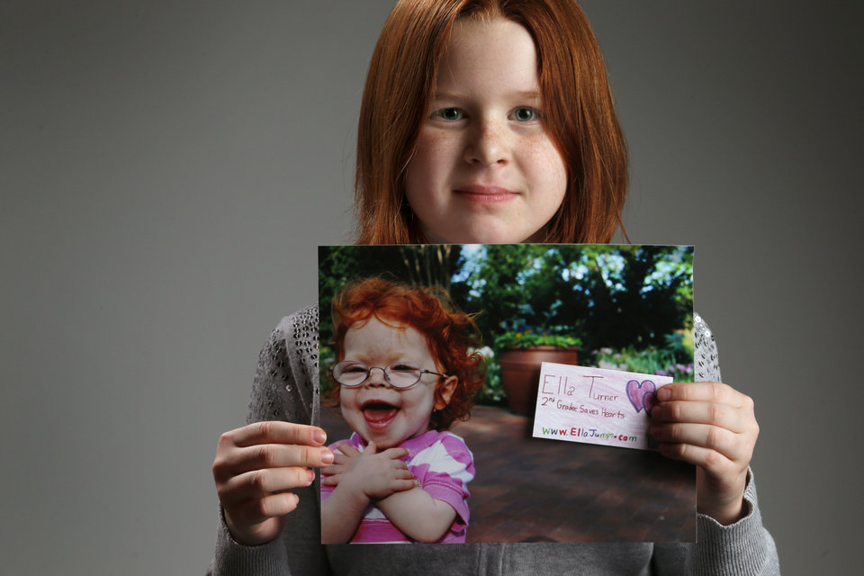 Ella Turner, 8, holds a photo of her 2-year-old sister, Colby, who died from a disease that affected her heart. Ella is raising money for the American Heart Association.