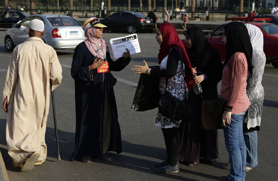 Photo - An Egyptian activit encourages passerbys to sign a petition by Tamarod, Arabic for