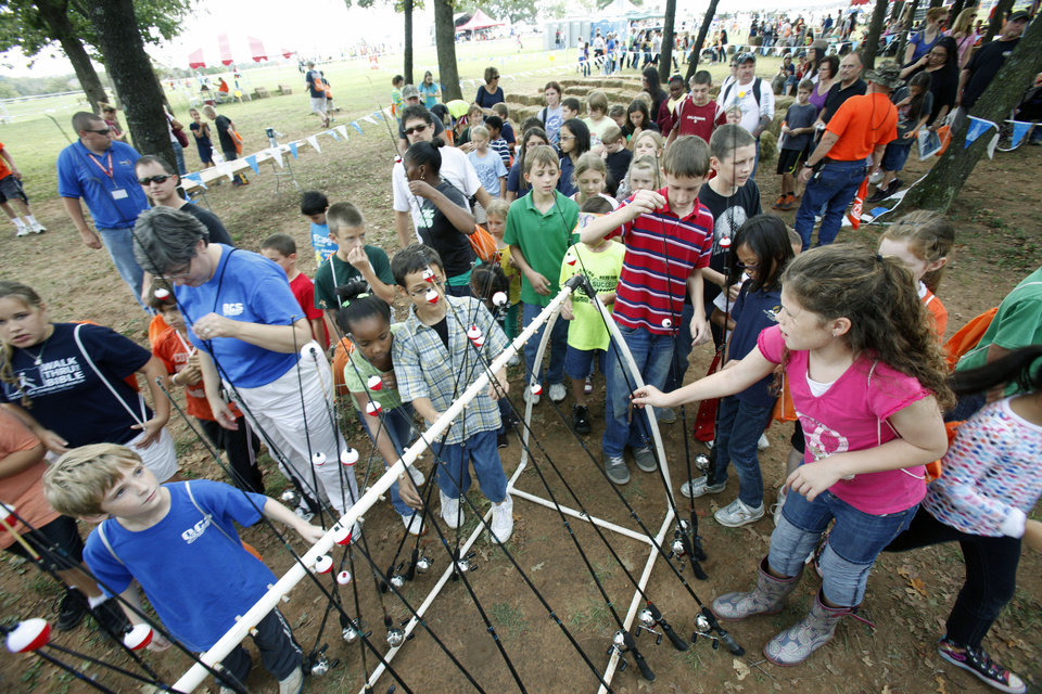Photo - Children choose fishing poles during school day of the Oklahoma Wildlife Expo at the Lazy E Arena and Ranch in Guthrie, OK, Friday, September 28, 2012,  By Paul Hellstern, The Oklahoman