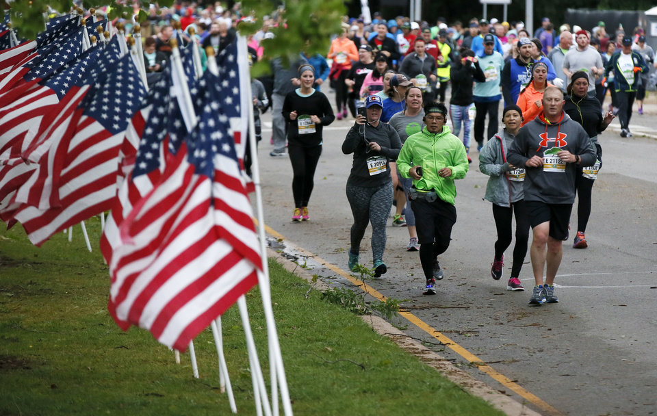 Photo - Runners pass the Field of Flags honoring child abuse victims on N Lincoln Blvd. south of the state Capitol during the Oklahoma City Memorial Marathon in Oklahoma City, Sunday, April 30, 2017. Photo by Nate Billings, The Oklahoman