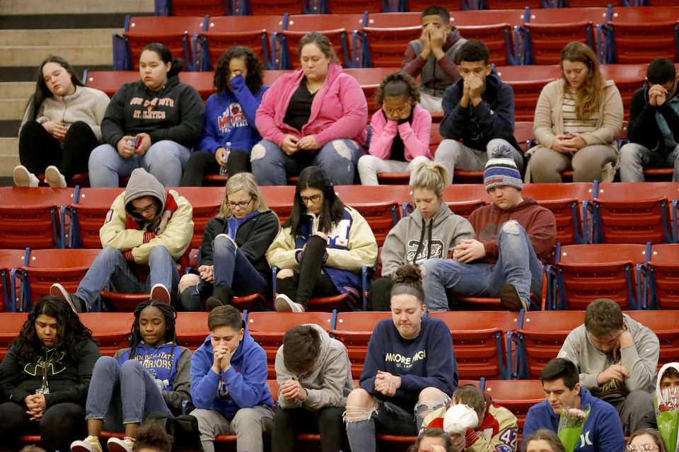 Photo - Community members pray during a vigil for students killed and injured in Monday's hit and run incident in Moore at Moore High School  in Moore, Okla., Tuesday, Feb. 4, 2020.  [Sarah Phipps/The Oklahoman]