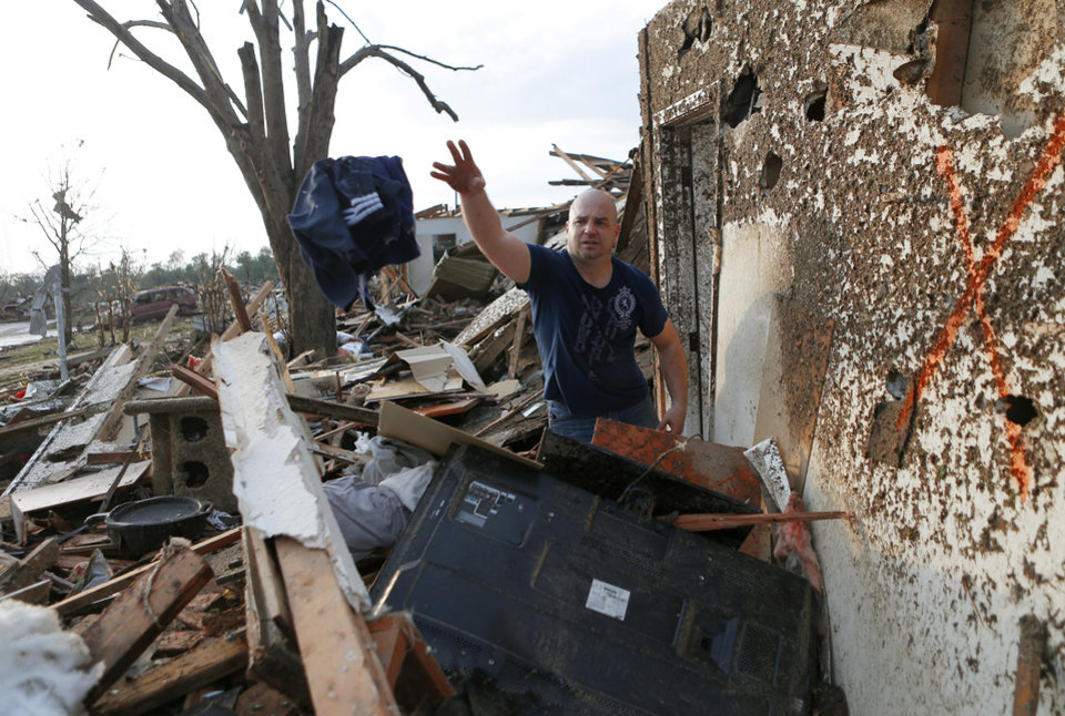 Nathan Carey salvages clothes from his brothers home in a residential area near Telephone Road in Moore, Okla., on Monday, May 20, 2013, after a tornado moved through the area. Photo by Bryan Terry, The Oklahoman