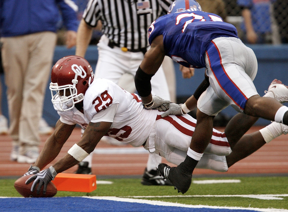 Photo - Oklahoma's Chris Brown (29) dives into the end zone to score a touchdown past Kansas' Darrell Stuckey (25) during the second half of the college football game between the University of Oklahoma Sooners (OU) and the University of Kansas Jayhawks (KU) on Saturday, Oct. 24, 2009, in Lawrence, Kan. Oklahoma won the game 35-13. Photo by Chris Landsberger, The Oklahoman