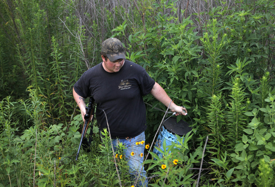 Josh Kinsey carries a hog feeder out of a  densely wooded area during a hunting trip near Indianola, Okla., Saturday, July 7, 2012.  Photo by Garett Fisbeck, The Oklahoman