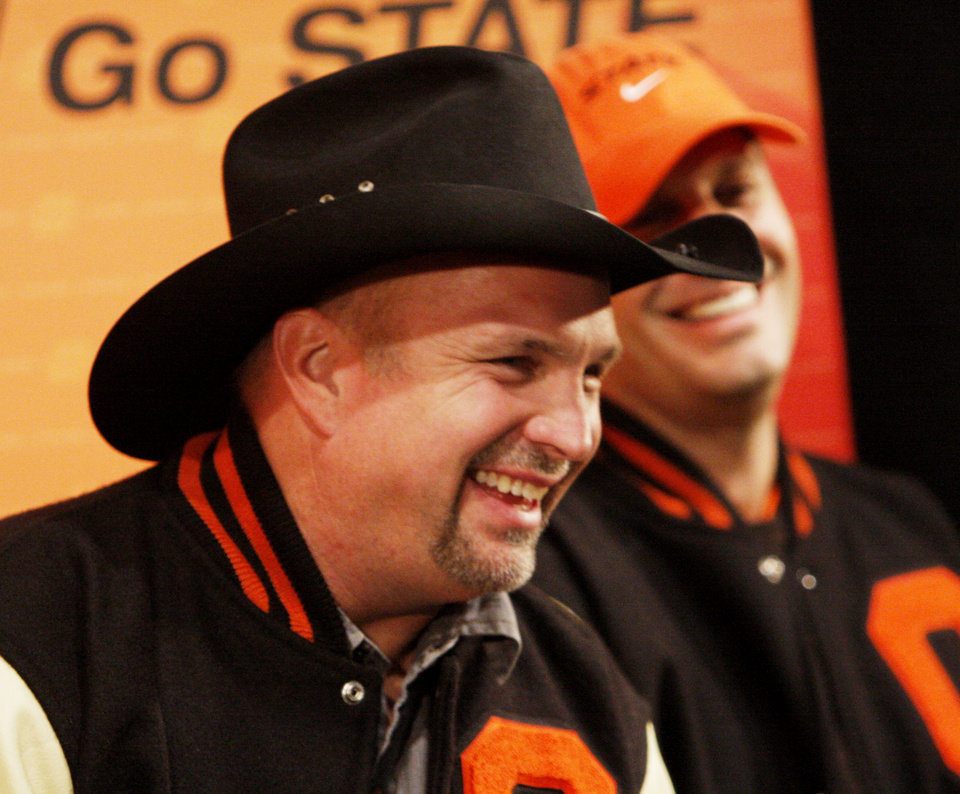 Photo - Garth Brooks and Robin Ventura share a laugh during the press conference before the college football game between Oklahoma State University (OSU) and the University of Missouri (MU) at Boone Pickens Stadium in Stillwater, Okla. Saturday, Oct. 17, 2009.  Photo by Doug Hoke, The Oklahoman