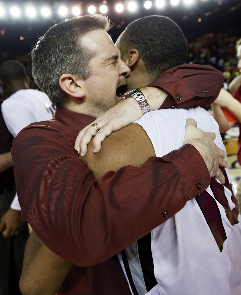 Photo - Edmond Memorial head coach Shane Cowherd hugs Jordan Woodard (10) after he made the game-winning tip-in against Midwest City during the Class 6A boys championship high school basketball game in the state tournament at the Mabee Center in Tulsa, Okla., Saturday, March 9, 2013. Edmond Memorial won, 49-48. Photo by Nate Billings, The Oklahoman
