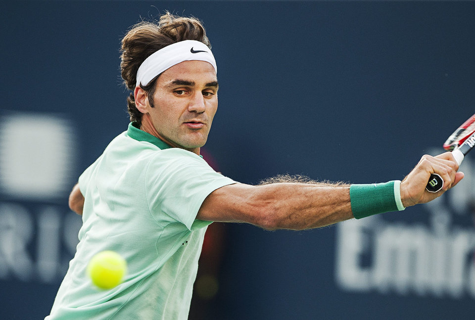 Photo - Roger Federer, of Switzerland, returns the ball against Canada's Peter Polansky during the Rogers Cup men's tennis tournament in Toronto on Tuesday, Aug. 5, 2014. (AP Photo/The Canadian Press, Aaron Vincent Elkaim)