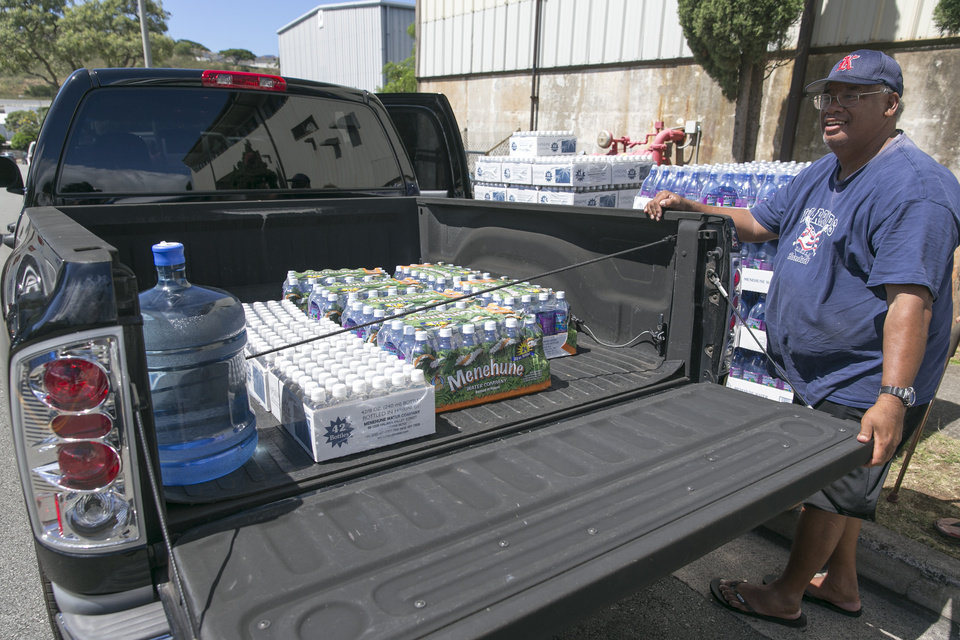 Photo - Honolulu resident Stan Nuuhiwa fills his truck with cases of water from the Menehune Water Company, Thursday, Aug. 7, 2014, in Aiea, Hawaii.  Hawaii is bracing for two back to back hurricanes, Iselle and Julio, which are on course to hit the Islands.  Bottles of water are quickly disappearing off shelves in Hawaii causing many people to line up for several hours to purchase water directly from the company.  (AP Photo/Marco Garcia)