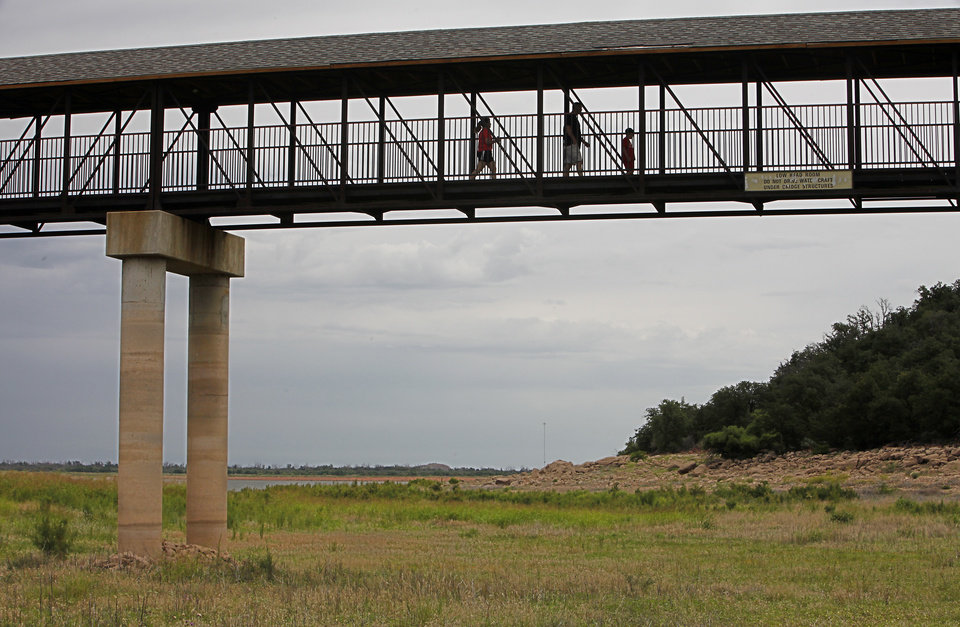 Photo - Drought. A family walks across a bridge that should be over water at the Quartz Mountain Conference Center on Lake Altus-Lugert near Altus,  June 30, 2014.   Photo by David McDaniel, The Oklahoman