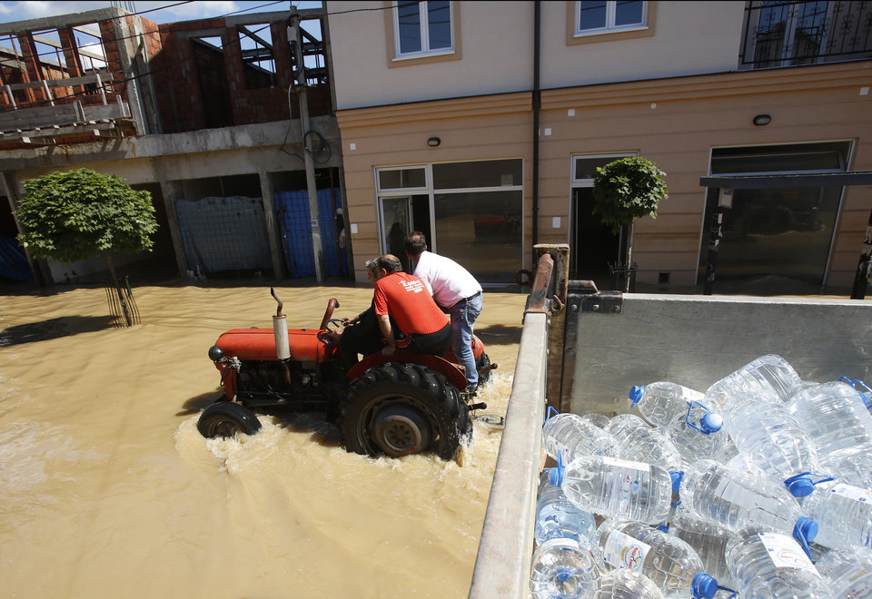 Photo - People ride on tractor in a flooded street in Obrenovac, some 30 kilometers (18 miles) southwest of Belgrade, Serbia, Monday, May 19, 2014. Belgrade braced for a river surge Monday that threatened to inundate Serbia's main power plant and cause major power cuts in the crisis-stricken country as the Balkans struggle with the consequences of the worst flooding in southeastern Europe in more than a century. At least 35 people have died in Serbia and Bosnia in the five days of flooding caused by unprecedented torrential rain, laying waste to entire towns and villages and sending tens of thousands of people out of their homes, authorities said. (AP Photo/Darko Vojinovic)