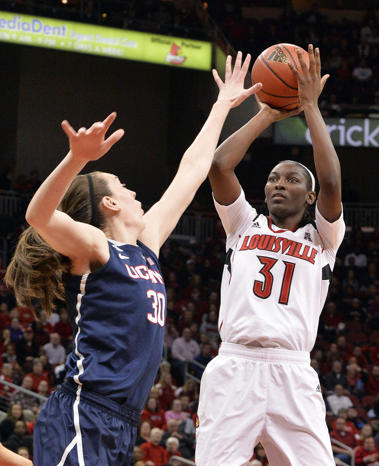 Photo - Louisville's Asia Taylor, right, puts up a shot over the defense of Connecticut's Breanna Stewart during the first half of an NCAA college basketball game, Monday, March 3, 2014, in Louisville, Ky. (AP Photo/Timothy D. Easley)