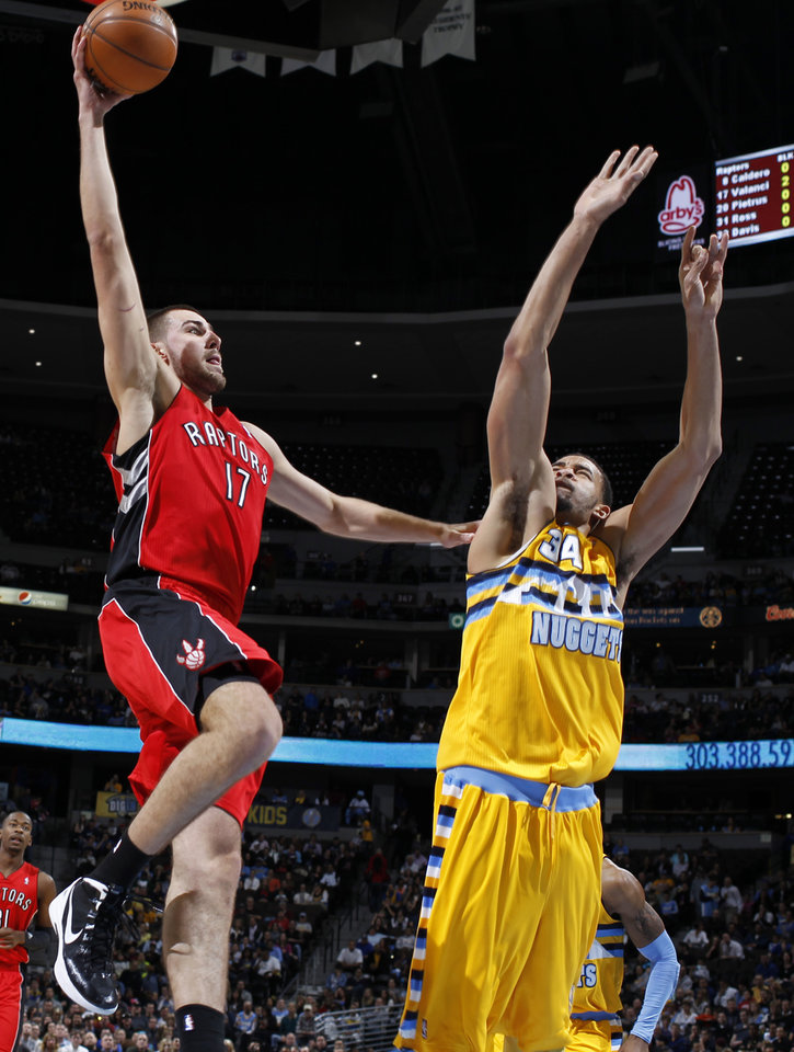 Toronto Raptors center Jonas Valanciunas, left, of Lithuania, goes up for a shot as Denver Nuggets forward JaVale McGee defends during the first quarter of an NBA basketball game in Denver on Monday, Dec. 3, 2012. (AP Photo/David Zalubowski)