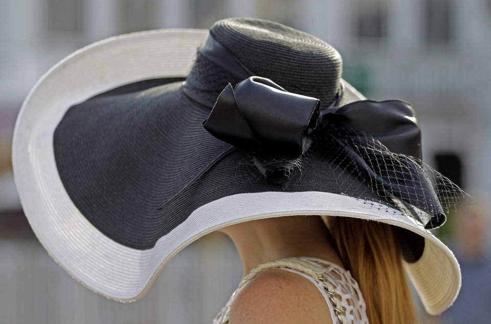 Photo - Carrie Cooke, Louisville, Ky., wears a fancy hat while walking through the paddock before the 138th Kentucky Derby horse race at Churchill Downs Saturday, May 5, 2012, in Louisville, Ky. (AP Photo/Mark Humphrey)  ORG XMIT: DBY110