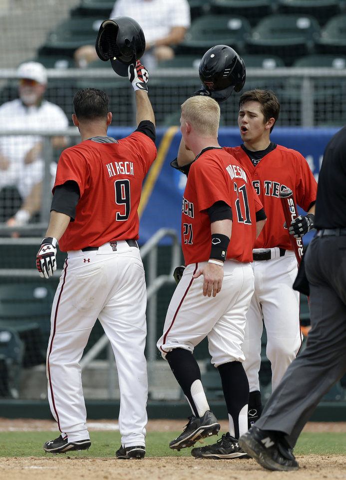 Photo - Texas Tech's Adam Kirsch (9) is congratulated by teammates after hitting a two-run home run against Columbia during the fifth inning of an NCAA college baseball regional tournament game in Coral Gables, Fla., Friday, May 30, 2014. Texas Tech's Bryant Burleson (21) also scored on the home run. (AP Photo/Alan Diaz)