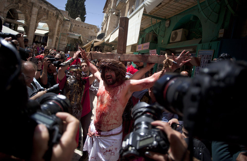 Photo - A Christian pilgrim dressed as Jesus Christ is attached to a cross during a reenactment of the crucifixion during a Good Friday procession in Jerusalem's Old City, Friday, March 29, 2013.  Less than 2 percent of the population of Israel and the Palestinian territories is Christian, mostly split between Catholicism and Orthodox streams of Christianity. Christians in the West Bank wanting to attend services in Jerusalem must obtain permission from Israeli authorities. Israel's Tourism Ministry said it expects some 150,000 visitors in Israel during Easter week and the Jewish festival of Passover, which coincide this year. (AP Photo/Sebastian Scheiner)